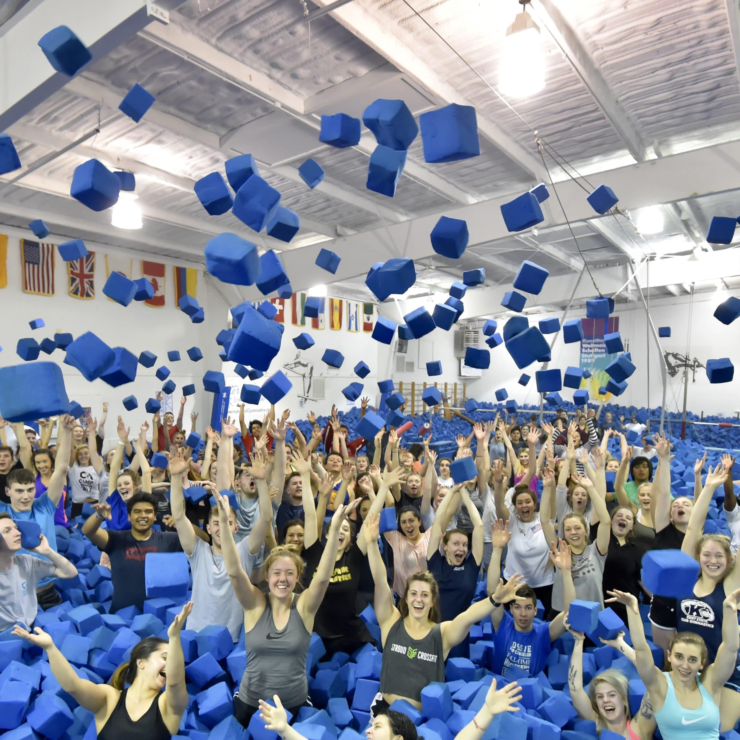 Big group of staff throwing blue blocks into the air