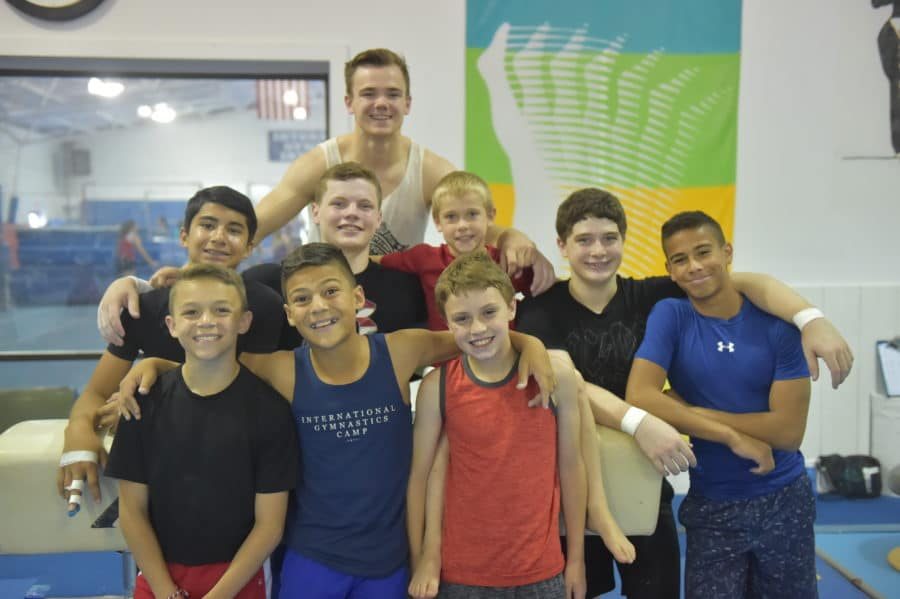 Group of boys with staff member smiling for photo