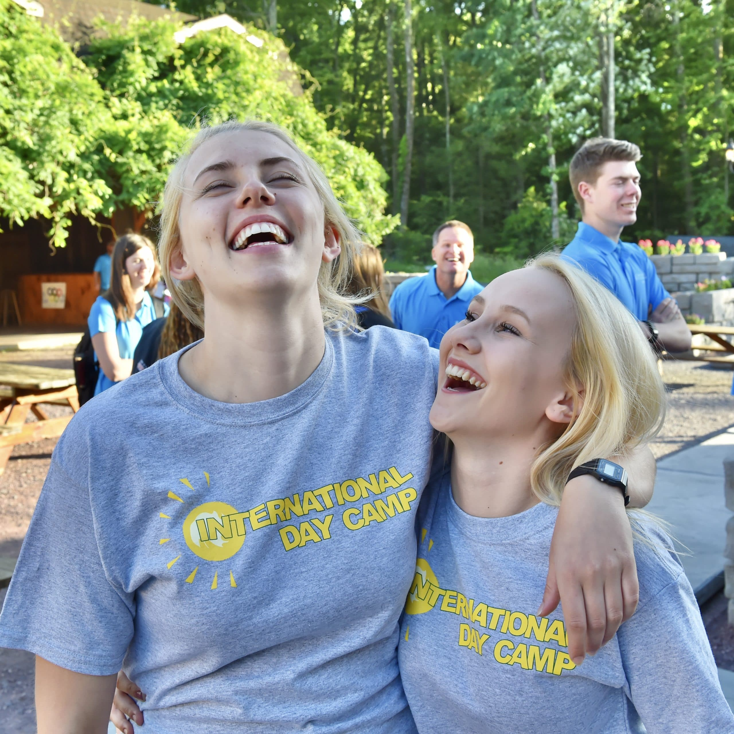 Two female staff members laughing outdoors