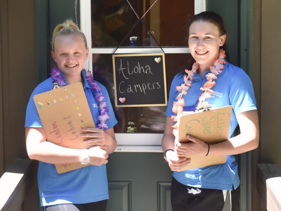Two female staff members holding clip boards and wearing leis