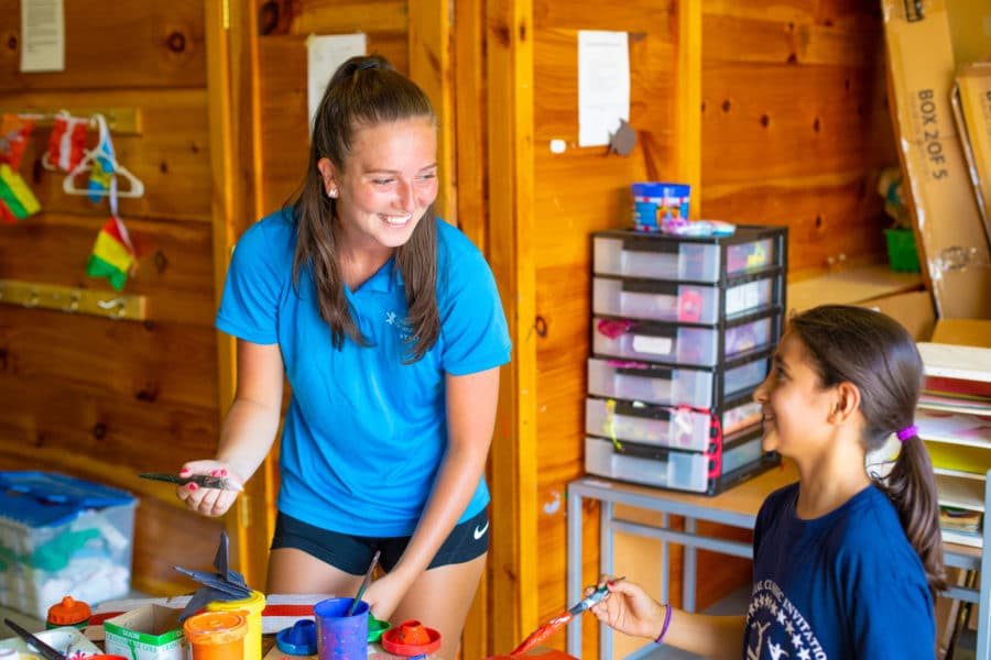 female staff member laughing with camper while doing crafts